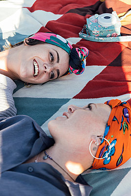 young women lying on a blanket laughing, Seville, Spain - p300m2253016 von Julio Rodriguez