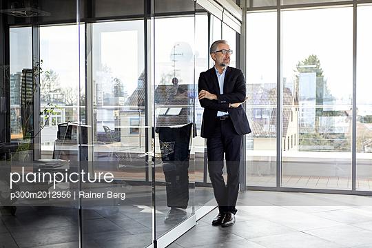 Businessman standing in office thinking - p300m2012956 von Rainer Berg