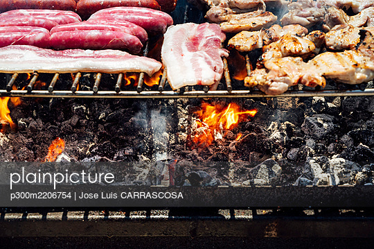 Close-up of meat and coals on barbecue grill in yard - p300m2206754 by Jose Luis CARRASCOSA