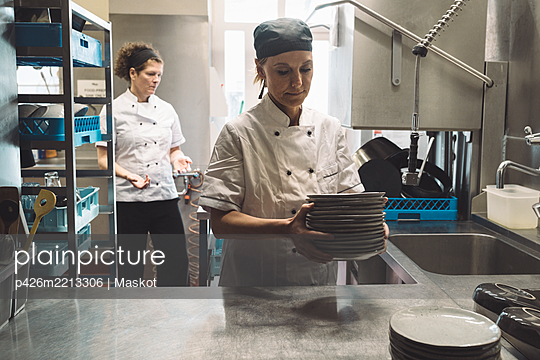 Female chef holding plates while coworker standing in background in commercial kitchen - p426m2213306 by Maskot
