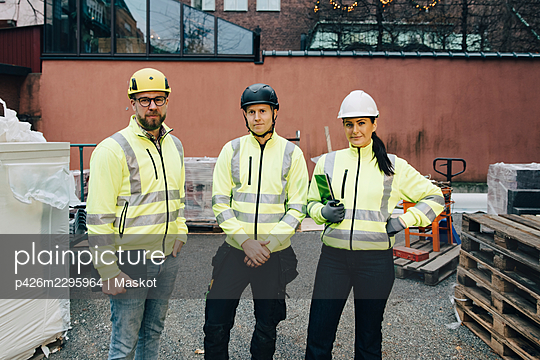 Portrait of male and female engineers standing together at construction site - p426m2295964 by Maskot