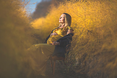 Pregnant woman sitting on chair in asparagus field in autumn - p300m2069005 by Anke Scheibe