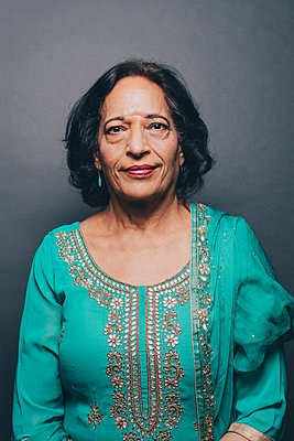 Portrait of confident senior woman wearing salwar kameez on gray background - p426m1588524 by Maskot