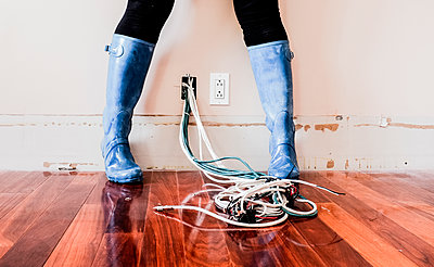 Caucasian woman wearing rain boots over electrical wiring - p555m1409527 by Shestock