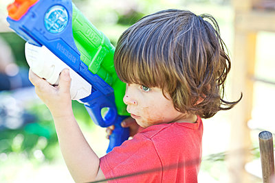Little boy playing with water gun - p699m2043662 by Sonja Speck