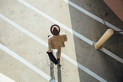 Young man walking across road, overhead view - p924m1493816 by Ashley Corbin-Teich