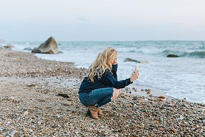 Young woman crouching on beach looking at smartphone, Menemsha, Martha's Vineyard, Massachusetts, USA - p924m2058136 by Lena Mirisola