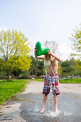 Canada, Kingston, Shirtless boy pouring water from rubber boot on head - p924m2283068 by Viara Mileva