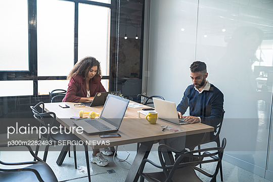 Male and female professionals working on laptop at coworking office - p300m2282493 by SERGIO NIEVAS