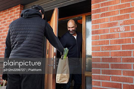 Man having shopping delivered - p312m2299727 by Plattform
