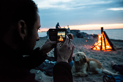 Man taking photographs of campfire on beach - p1142m1362244 by Runar Lind