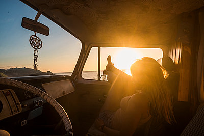 Spain, Tenerife, young woman lying in a van at sunset - p300m1535822 by Simona Pilolla