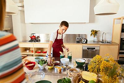 Woman preparing food in kitchen - p300m1586940 by Bonninstudio