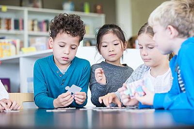 Pupils playing jigsaw puzzle in school together - p300m2004708 von Fotoagentur WESTEND61