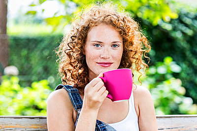 Portrait of redheaded young woman with pink coffee cup - p300m2029081 by Jo Kirchherr