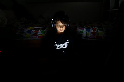 Portrait of boy sitting in his dark room using headphones and digital tablet - p300m2189539 by Valentina Barreto
