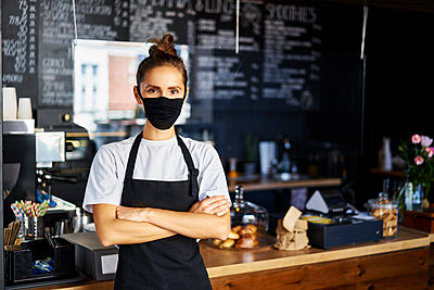Portrait of waitress in protective face mask with arms crossed standing at cafe - p300m2225132 by Bartek Szewczyk