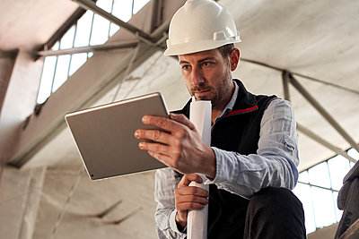 Serious male engineer using digital tablet while standing in building at site - p300m2243421 by Veam