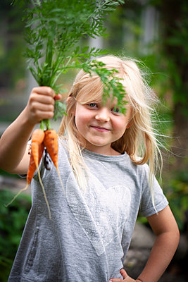 Smiling girl holding carrot - p312m2101898 by Matilda Lindeblad
