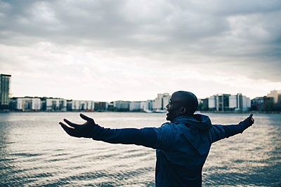 Male athlete standing with arms outstretched by sea against sky in city - p426m2036825 by Maskot