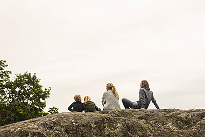 Family resting together on rock formation against clear sky - p426m2145645 by Maskot