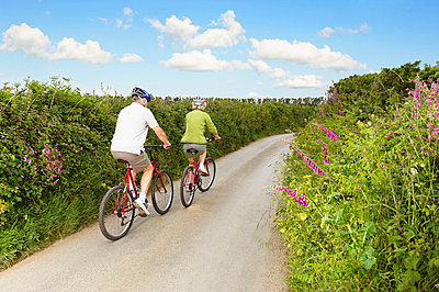 Senior couple cycling up country lane - p4292998f by Frank and Helena