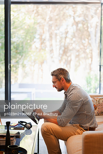 Businessman using digital tablet, working from home on sofa - p1023m2196662 by Paul Bradbury