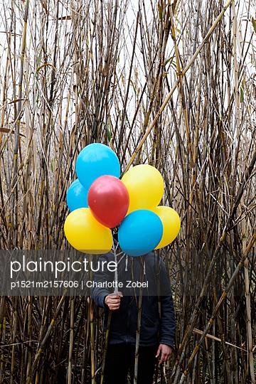Mann hält Luftballons - p1521m2157606 von Charlotte Zobel