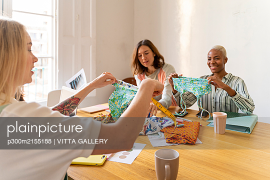 Fashion designers having a meeting in office - p300m2155188 by VITTA GALLERY