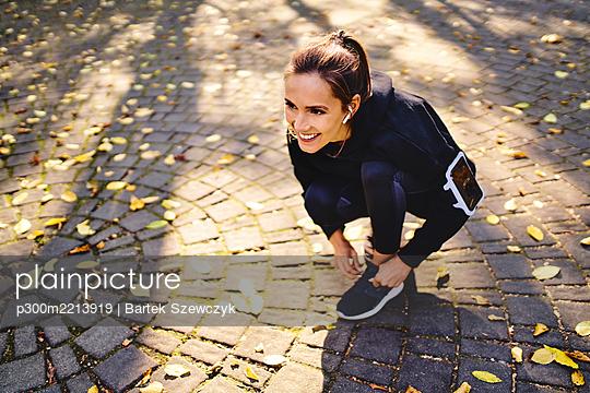 Young woman tying her running shoe - p300m2213919 by Bartek Szewczyk