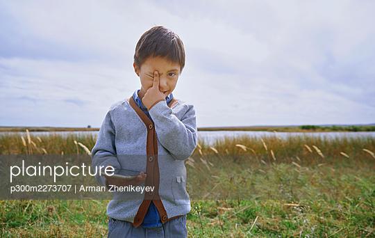 Boy with finger on eye holding smart phone - p300m2273707 by Arman Zhenikeyev