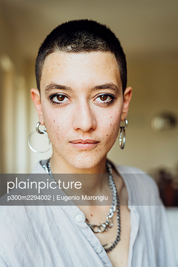Young woman with short hair wearing jewelry at home - p300m2294002 by Eugenio Marongiu