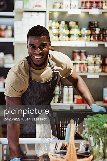 Portrait of smiling male owner with basket in deli store - p426m2270514 by Maskot