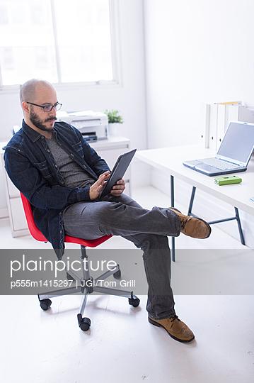 Hispanic businessman working at desk - p555m1415297 by JGI/Tom Grill