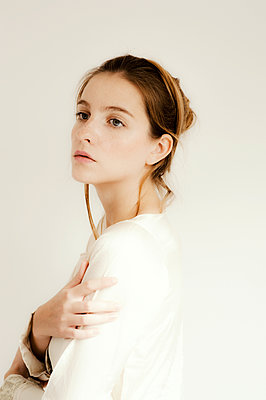 Beautiful woman in a white silk dress against a light background - p1047m1066113 by Sally Mundy