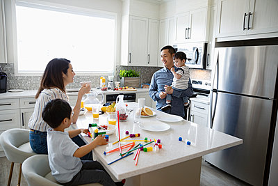 Family eating breakfast and playing with toys in morning kitchen - p1192m2088553 by Hero Images
