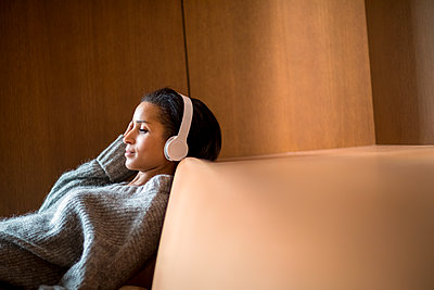 Portrait of relaxed young woman listening music with headphones on couch - p300m1549888 by Jo Kirchherr