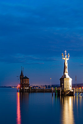 Germany, Constance, view to port entrance with lighthouse and Imperia at twilight - p300m1587308 by Werner Dieterich