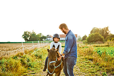Man helping his daughter ride horse in Friseboda, Sweden - p352m1536521 by Lina Roos