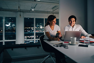 Smiling businessman and businesswoman planning strategy while looking at laptop in office - p426m2194757 by Maskot