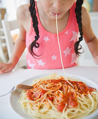 Mixed race girl eating spaghetti - p555m1479095 by JGI/Jamie Grill