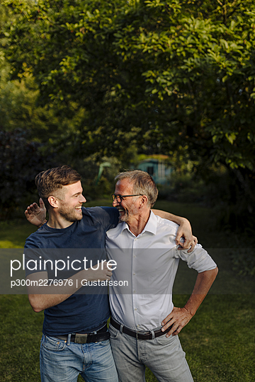 Happy father and son looking at each other while standing in back yard - p300m2276976 by Gustafsson