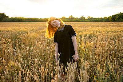 Junge Frau in einem Kornfeld bei Sonnenuntergang - p1646m2229928 von Slava Chistyakov