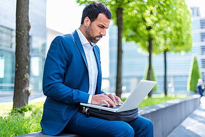 Businessman using laptop - p300m1587222 by Daniel Ingold