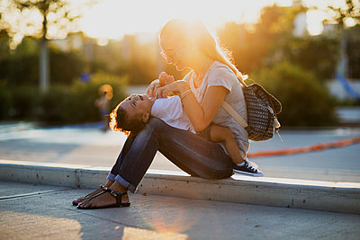 Happy mother playing with her little son on a square at sunset - p300m2059970 by Nasos Zovoilis