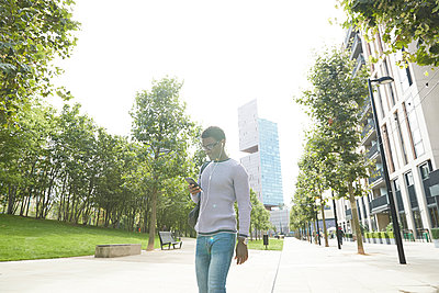 Male entrepreneur listening music through in-ear headphones while walking on footpath in city - p300m2241566 by Pete Muller