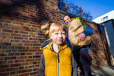 Cute blond girl standing against father carrying vegetables bag - p300m2277312 by Irina Heß