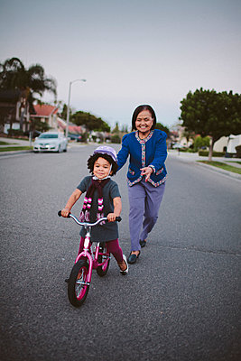 Grandmother teaching granddaughter to ride bicycle on suburban street - p555m1409614 by Shestock