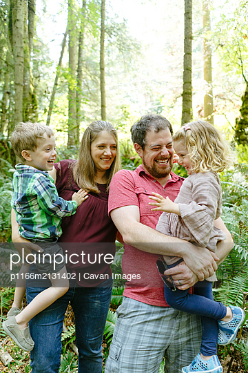 Closeup portrait of a family laughing together on a forest hike - p1166m2131402 by Cavan Images