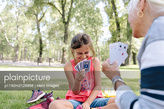 Granddaughter and grandmother playing cards in park - p1192m2129958 by Hero Images